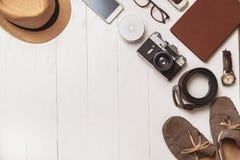 Reeks toebehoren van de mensen` s zomer voor de reiziger op een witte houten achtergrond stock afbeelding