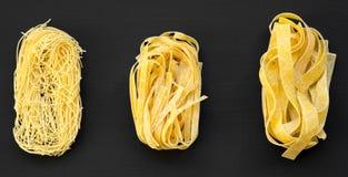 Reeks van diverse ongekookte deegwaren: fettuccine, pappardelle, tagliolini op donkere zwarte achtergrond, luchtmening stock afbeeldingen