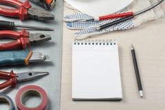 Reeks van elektrohulpmiddelen, witte helm en blocnote op metaalachtergrond Het concept van de energie Stock Afbeeldingen