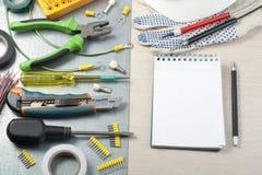 Reeks van elektrohulpmiddelen, witte helm en blocnote op metaalachtergrond Het concept van de energie Stock Foto
