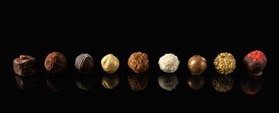 Reeks van het fijne Wit, dark en de melkchocola van het chocoladesuikergoed op zwarte achtergrond met bezinning royalty-vrije stock foto