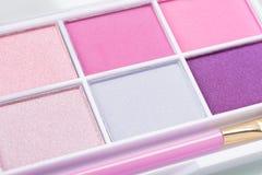 Reeks van oogschaduw in roze kleuren met een borstel op een lichte achtergrond, close-up royalty-vrije stock afbeeldingen