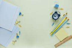 Reeks van schoolkantoorbehoeften terug naar school: potloden, klok, blocnote, heerser op gele achtergrond onderwijs, les stock foto