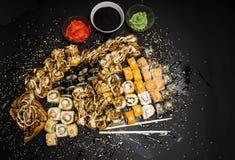 Reeks van traditioneel Japans voedsel op een donkere achtergrond Sushibroodjes, nigiri, ruw zalmlapje vlees, rijst, roomkaas royalty-vrije stock foto's