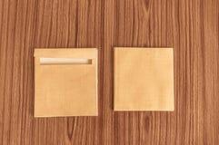 Reeks van twee Bruine envelopvoorzijde en rug die op houten de vloerachtergrond van het lijsthardhout wordt geïsoleerd Adreskaart stock foto