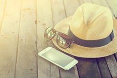 Reeks van vakantietoebehoren zoals mobiele telefoon, glazen, hoed op houten uitstekende achtergrond Stock Fotografie
