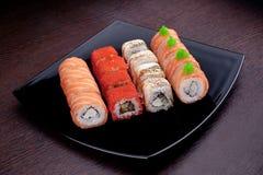 Reeks van verschillende sushimaki op zwarte plaat Japans voedsel op achtergrond Stock Foto