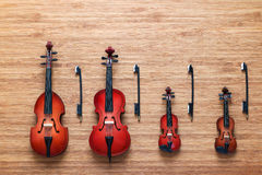 Reeks van vier stuk speelgoed instrumenten van het koord muzikale orkest: viool, cello, contrabas, altviool op een houten achterg Royalty-vrije Stock Afbeeldingen