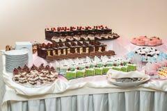 Reeks verschillende die cakessnoepjes en desserts op één plaat worden geschikt De bar van het partijsuikergoed stock afbeeldingen