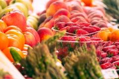 Reeks vruchten en groenten in een pakhuis Kleurrijke aardbeien, appelen en perziken op vertoning stock fotografie
