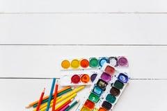 Reeks waterverfverven en penselen op een lijst Royalty-vrije Stock Afbeelding