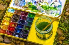 Reeks waterverfverven en penselen voor het schilderen van close-up stock afbeelding