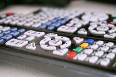 Reeks zwarte afstandsbedieningen met kleurrijke knopen op witte oppervlakte als symbool van huisvermaak wanneer het letten van op Royalty-vrije Stock Foto