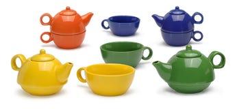 Reeksen gekleurde ceramische theepotten en mokken op wit Stock Afbeeldingen