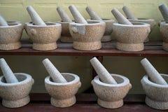 Reeksen van mortier en stamper in de lichtgrijze steen die van het kleurengraniet op houten plank voor verkoop in lokale markt sc Stock Fotografie