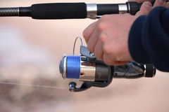 Reel 1. A close up shot of a hand holding a fishing rod stock image
