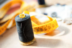 Reel of black thread with a needle on a workbench Stock Images