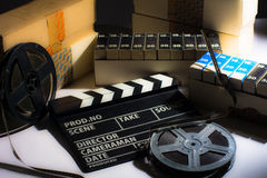 Reel with film and cinema clap. Motion picture films in boxes Royalty Free Stock Images