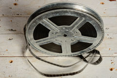 Reel of film in retro. Movie reel on a  white wooden background Stock Photos