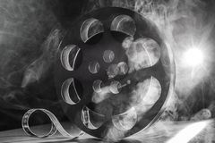 Reel of film retro in the smoke. black and white. Movie reel of film in retro in the smoke black and white on a dark background Stock Photos
