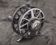Reel fishing rod. On a stone background royalty free stock images
