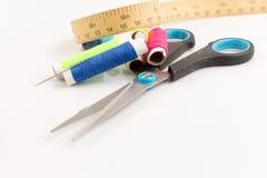 Reel med scissor och mäta bandet på vit Arkivbild