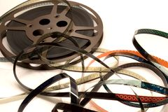 A Reel Mess I. A film reel unwinds and spills into a spaghetti mess.  Focus is on the film strip with 3 and 4 viewable Royalty Free Stock Images