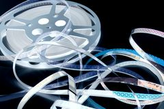 A Reel Mess I. A film reel unwinds and spills into a spaghetti mess.  Focus is on the film strip with 3 and 4 viewable Stock Image