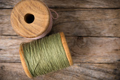 Reel pink with green yarn left side on wood Stock Photo
