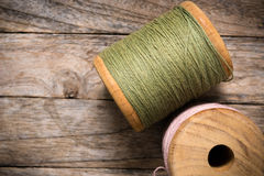 Reel pink with green yarn right side on wood Stock Photo