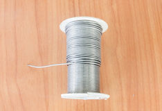 Reel of Solder placed on a wooden table royalty free stock photography