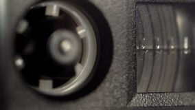 Reel of a vintage audio cassette with a magnetic tape macro rotating in the tape recorder