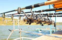 Reels with rods on a special stand with bite alarms. Reels with rods on a special stand with bite alarms on the jetty on a sunny day royalty free stock image