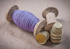 Reels of sewing threads thimbles on vintage background needlewor Stock Photos