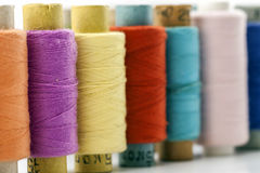 Reels or spools of multicolored sewing threads. Threads of all c Stock Photos
