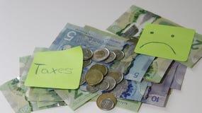 Reembolso de imposto canadense soletrado com telhas da letra e notas do dólar canadense fotografia de stock royalty free