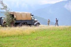 Reenactment histórico da batalha da guerra mundial 2 - o veículo e os soldados blindados de transporte vestiram-se em uniformes a Fotografia de Stock Royalty Free