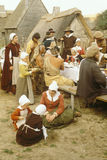Reenactment of Pilgrims and Indians dining Stock Images