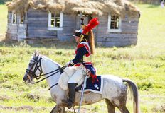 Reenactor穿戴了,拿破仑式的战争战士骑马 免版税图库摄影