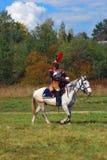 Reenactor胸甲骑兵骑一个白马 秋天树背景 免版税库存图片