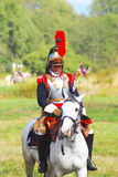 Reenactor-cuirassier dressed as Napoleonic war soldier rides a horse. Stock Photos