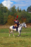 Reenactor cuirassier rides a white horse. Autumn trees background. Royalty Free Stock Image
