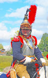 Reenactor dressed as Napoleonic war French soldier rides a horse. Royalty Free Stock Images