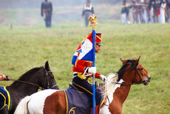 Reenactor dressed as Napoleonic war soldier carries a French flag. Royalty Free Stock Photos