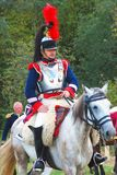 Reenactor dressed as Napoleonic war soldier rides a horse. Royalty Free Stock Images