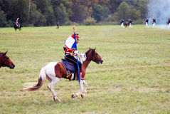 Reenactor dressed as Napoleonic war soldier rides a horse. Royalty Free Stock Photos