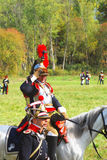Reenactor dressed as Napoleonic war soldier rides a horse. Royalty Free Stock Photography