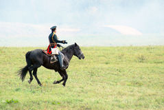 Reenactor dressed as Napoleonic war soldier rides a horse. Stock Photography