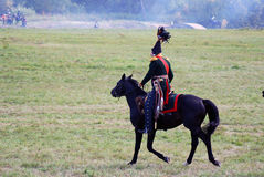 Reenactor dressed as Napoleonic war soldier rides a horse. Royalty Free Stock Photo