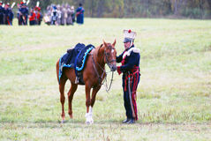 Reenactor dressed as Napoleonic war soldier stands by a horse. Royalty Free Stock Photo